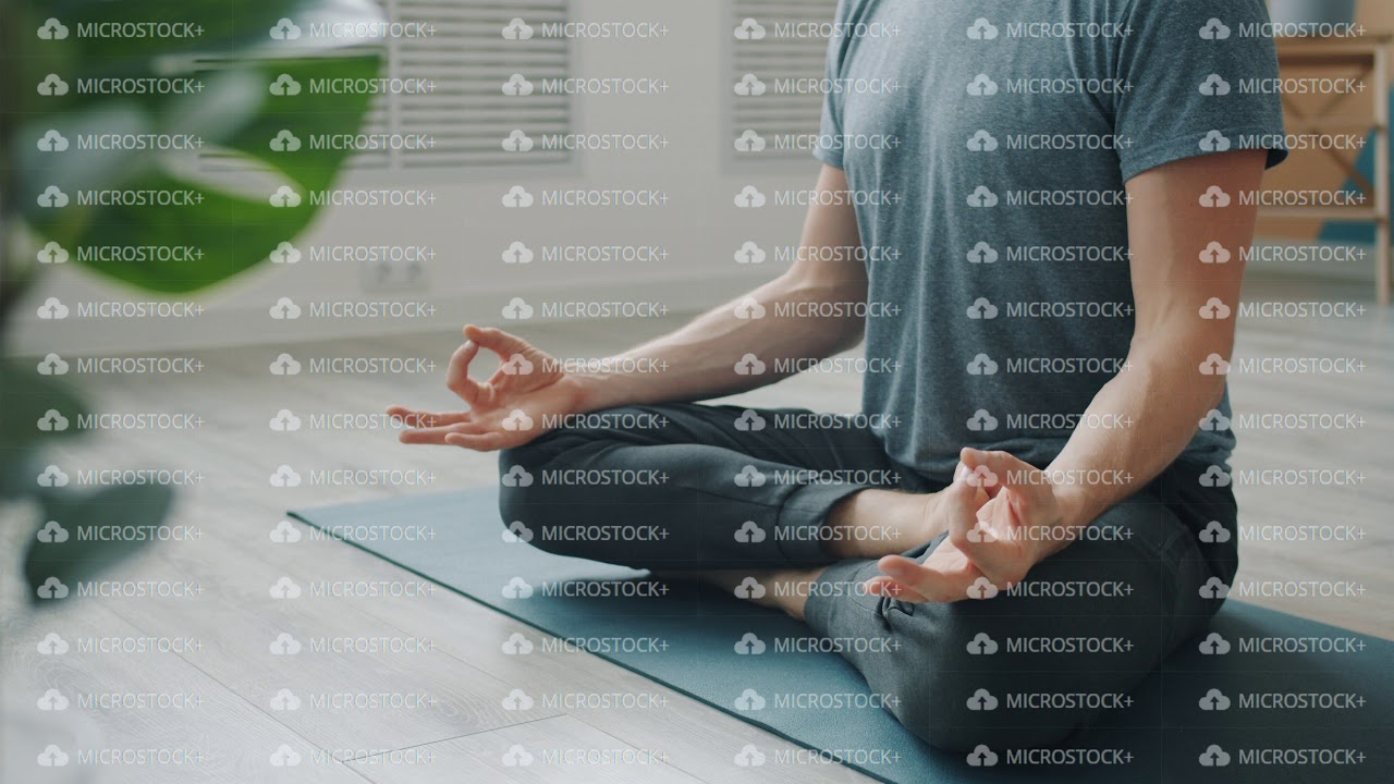 Low shot of anonymous man meditating on yoga mat sitting in lotus position