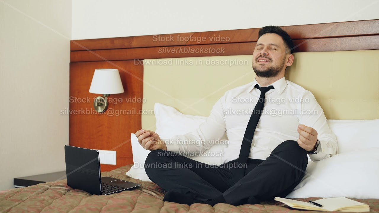 Smiling businessman put off laptop computer and taking yoga lotus position sitting relaxed on bed in