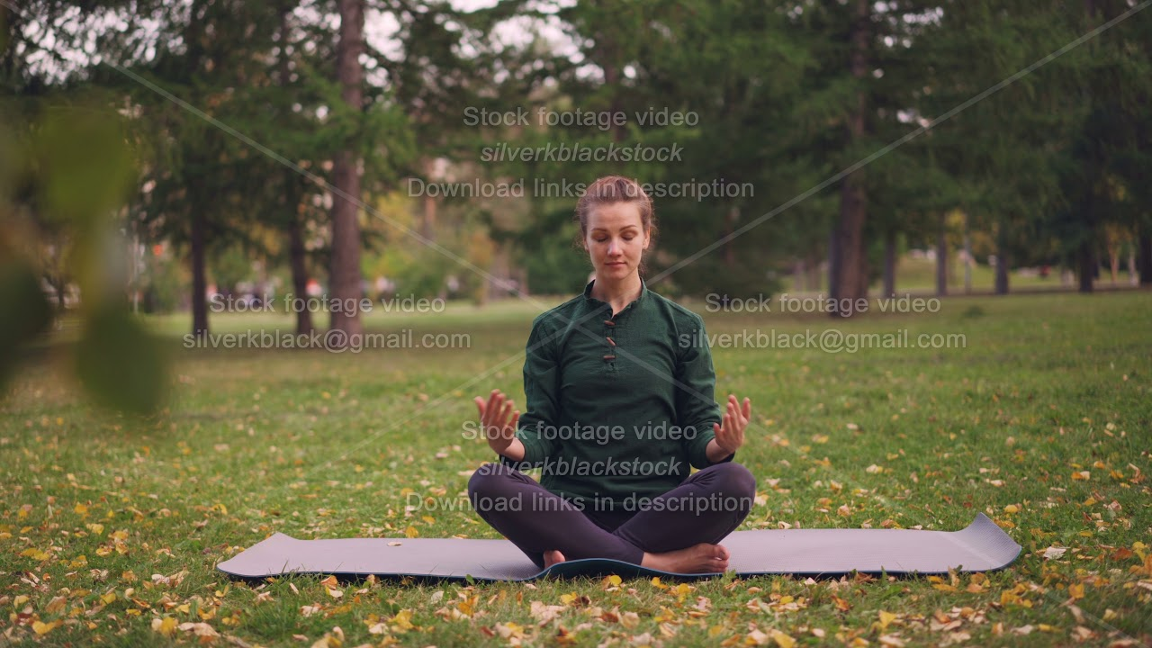 Good-looking girl is sitting in lotus position on yoga mat on grass in city park holding hands in